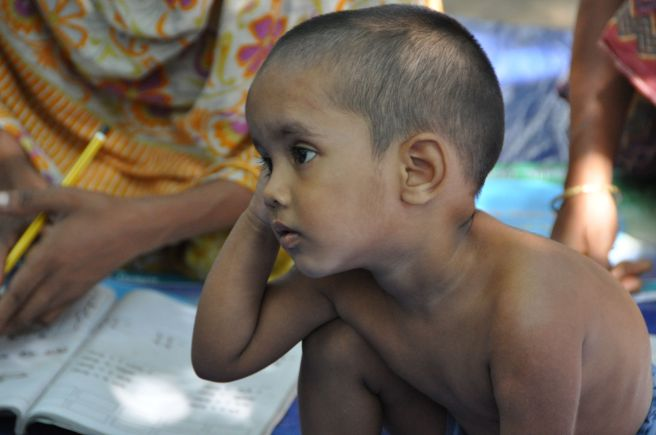 A child sitting next to his mother in class